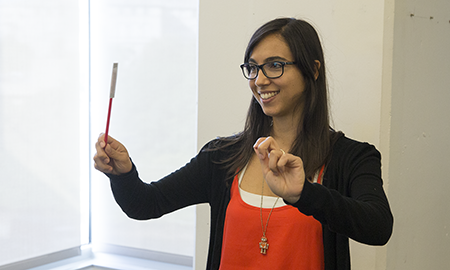 A woman conducts music with a PaperID wand