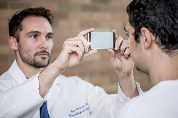 Dr. Lynn McGrath and Alex Mariakakis demonstrate PupilScreen