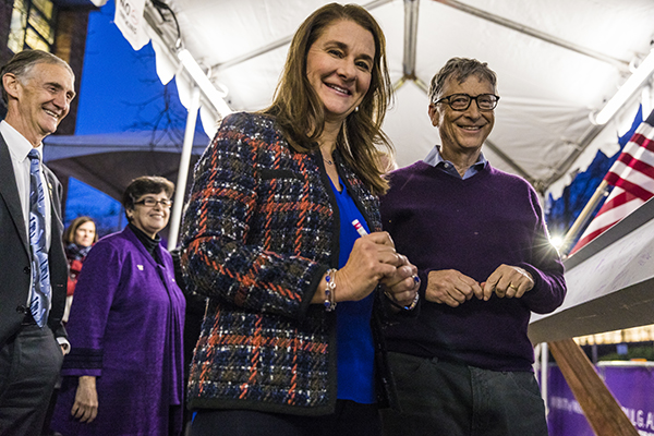 Melinda and Bill Gates sign the beam