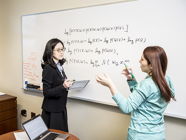 Su-In Lee and Safiye Celik discuss the MERGE formula written on a whiteboard