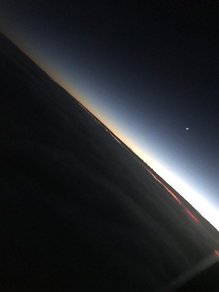 Photo of the moon and space above the curvature of the earth's surface