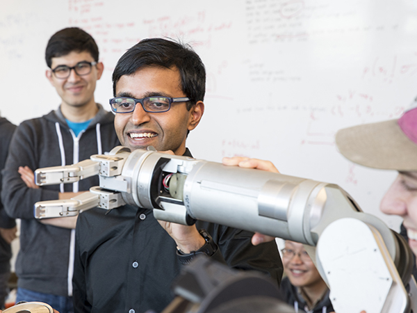 Sidd Srinivasa examining the positioning of a robot arm while members of his lab look on.