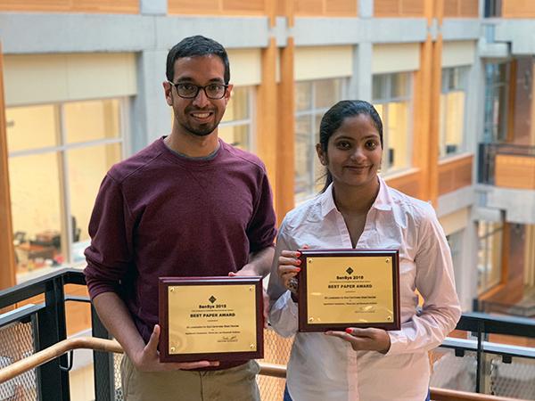 Vikram Iyer and Rajalakshmi Nandakumar holding their SenSys 2018 Best Paper Awards