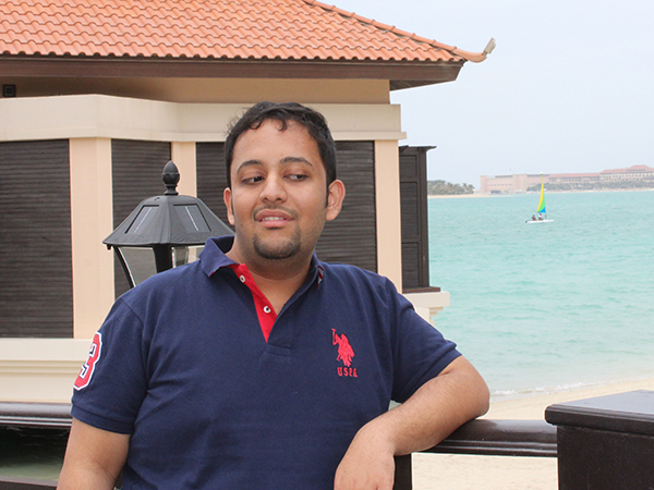 Venkatesh Potluri poses in a blue and red polo shirt against a railing overlooking a sandy beach and water, with a sailboat in the background