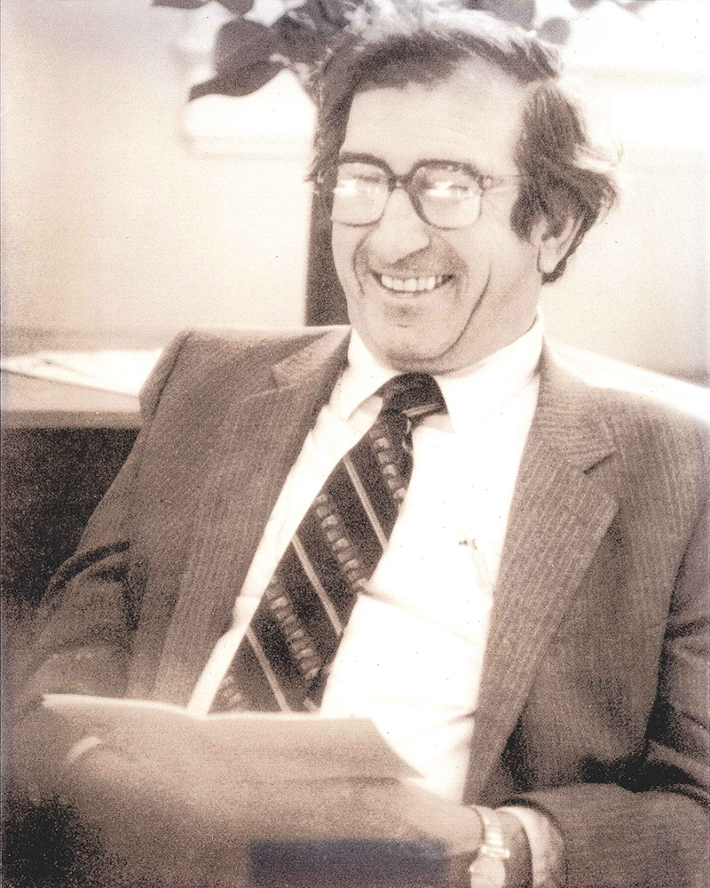 Black and white portrait of Hellmut Golde in suit and tie wearing glasses and smiling