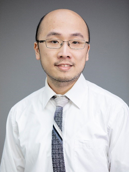 Portrait of Yin Tat Lee wearing glasses, a white dress shirt, and grey and black patterned tie