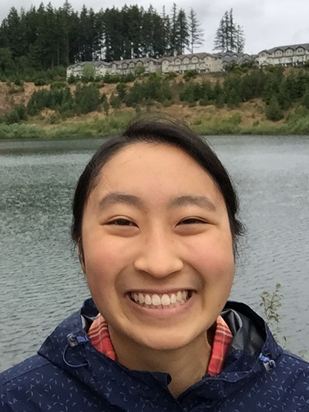 Christine Chen smiling in front of water with a grassy hill and building in background