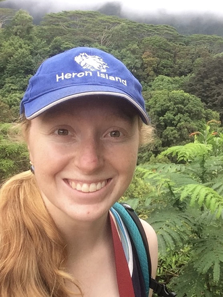 Erin Wilson in a hat smiling with foliage in background
