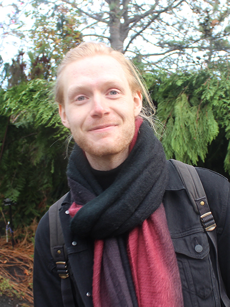 Peter West smiling in a scarf with trees in background