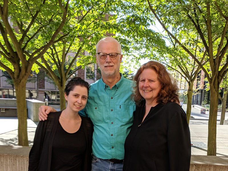 Left to right: Emma Notkin, Richard Ladner, and Cathy Tuttle smiling with trees and campus buildings in background