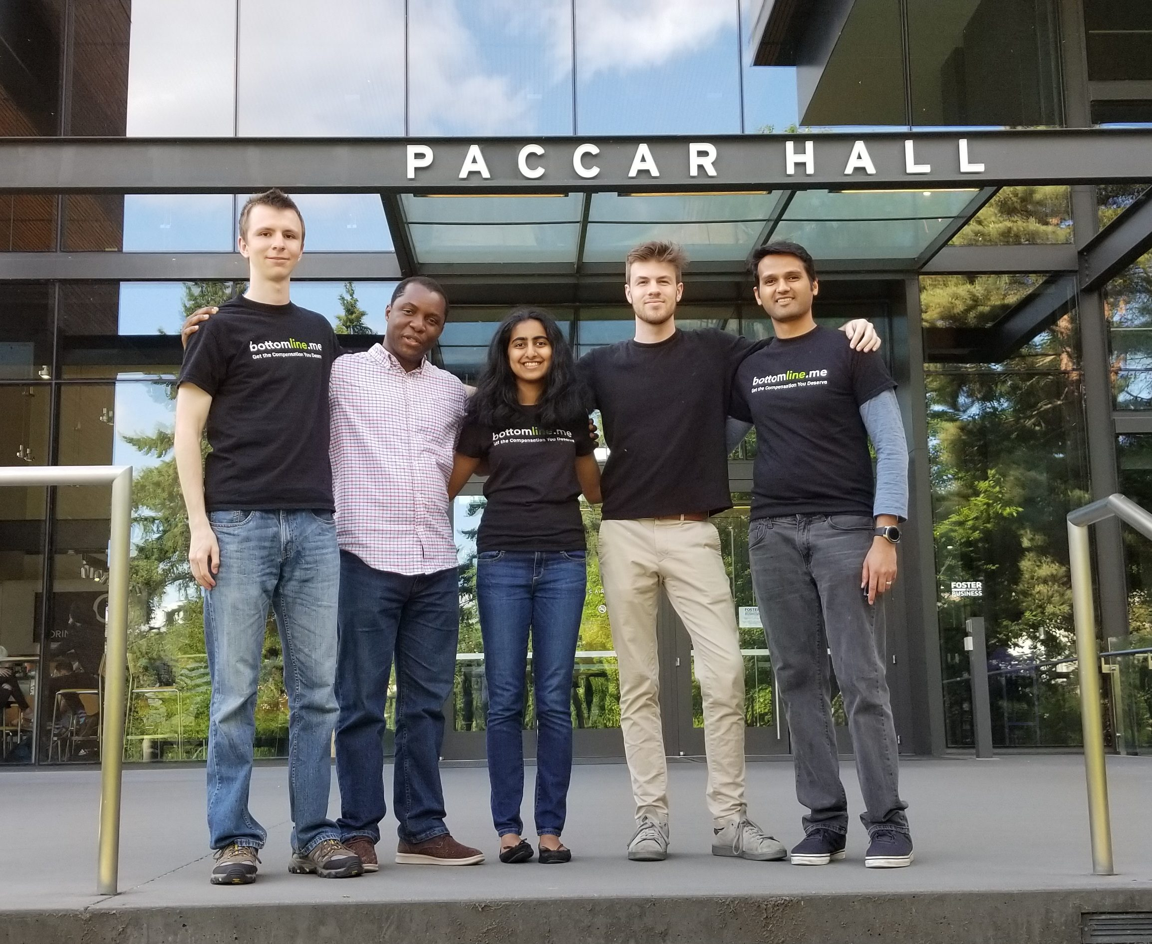 Five smiling students posed in front of Paccar Hall