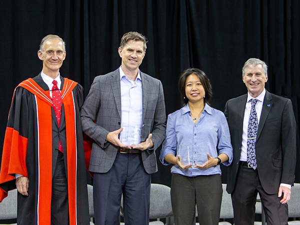 Three smiling men and one smiling woman. The man and woman in the center are holding glass award plaques.