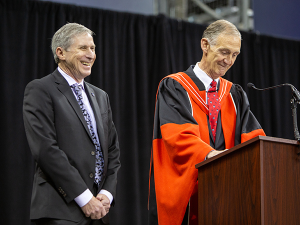 Laughing man in suit standing next to man in red and black robe smiling at podium