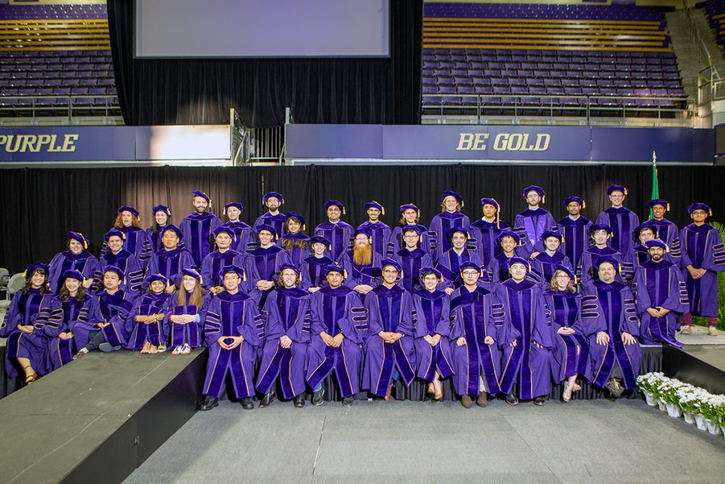 Group shot of Ph.D. graduates in purple robes with gold trim