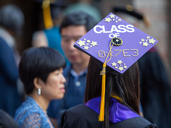 "Purple graduation cap and gold tassel decorated with gold stars and ""Class of 0x7E3"""