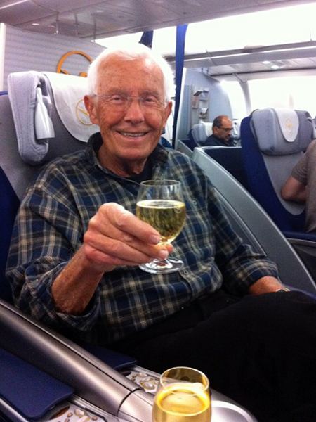 Smiling man wearing plaid shirt and glasses holding glass of wine seated on plane