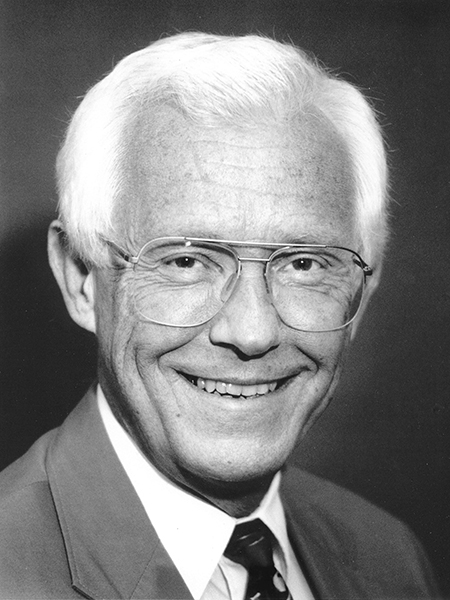 Greyscale portrait of smiling man wearing glasses