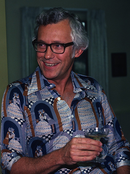 Smiling man wearing glasses and a patterned shirt, holding a champagne coupe