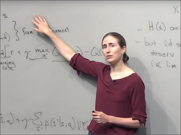 Woman pointing at white board.