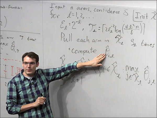 Man in glasses pointing at white board.