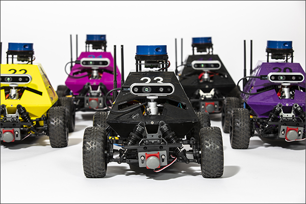 A group of robotic race cars in different colors against a plain white background