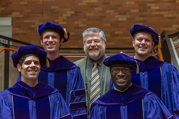 Four Ph.D. students in robes and caps with Gaetano Borriello