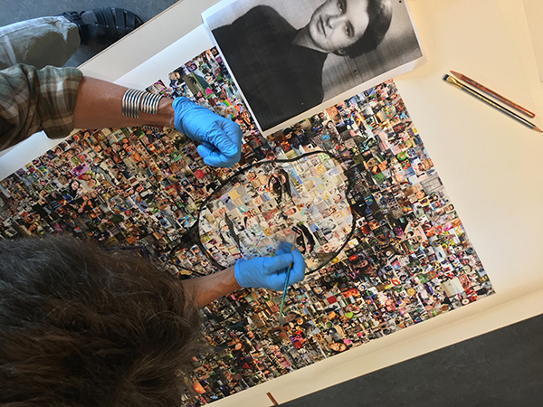 Action shot from above of artist Kate Thompson painting Rosalind Franklin's portrait over backdrop of images