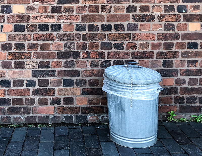 Metal garbage can in front of brick wall