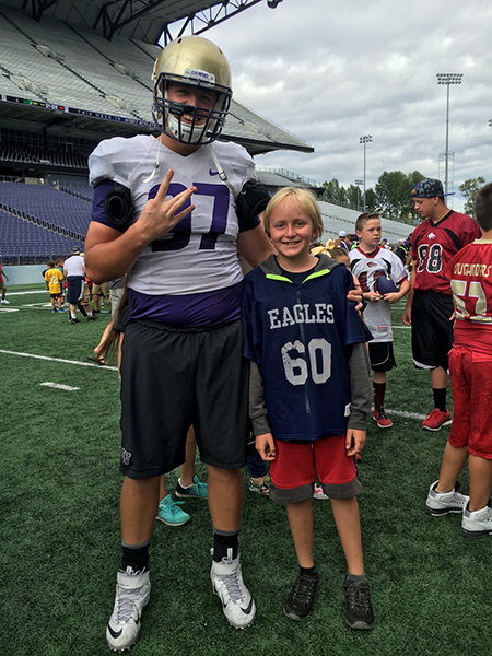 "UW Huskies football player makes the ""Dubs up!"" sign with his fingers, with his arm around Leo Maddox Schneider"