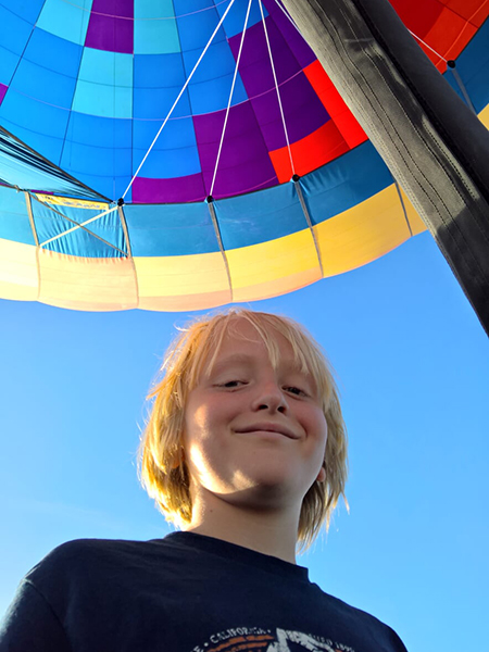 Leo Maddox Schneider smiling under a multi-colored canopy against a vivid blue sky