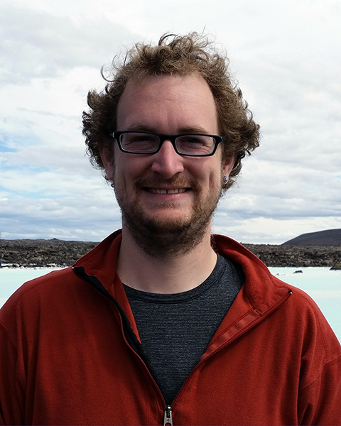 Portrait of Nicholas Bolten standing outside with water and pebbly beach in the background
