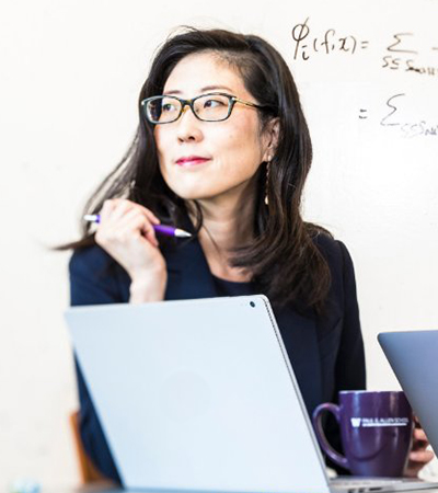 Su-In Lee holding pen with coffee mug and laptop