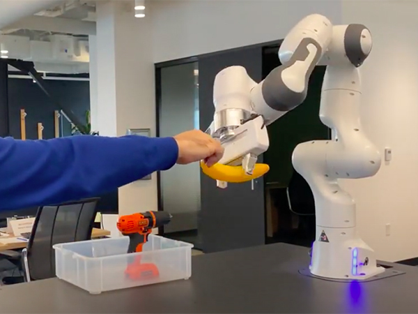 Person's arm and hand transferring banana to table-mounted robot arm and hand