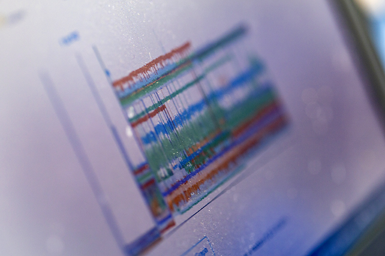Laptop screen showing squiggly lines of various colors stacked on top of each other, representing signals from a nanopore sensing device